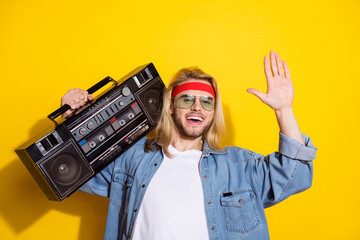 Photo of funky pretty young guy dressed denim shirt smiling waving arm palm holding boom box isolated yellow color background