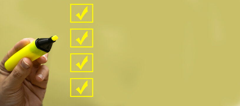 hand holding yellow felt pen and marking on checklist box. Checklist concept, copy space
