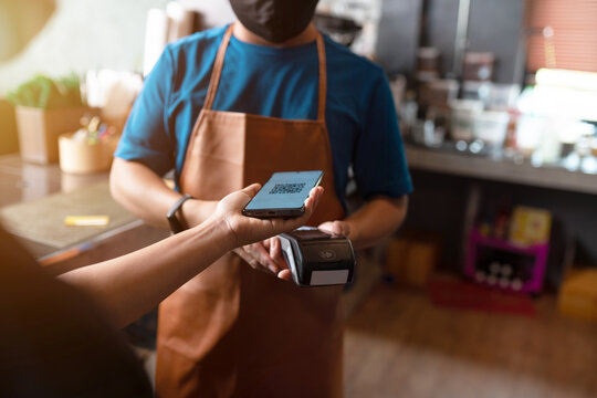 Paying with a QR code at a credit card machine in a coffee shop