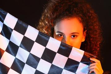 Fototapeta Beautiful young woman with racing flag on dark background, closeup obraz