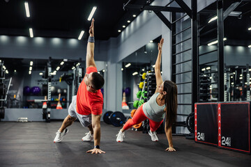 Fototapeta The fitness man and energetic woman are in a plank position with their arms raised and doing full-body in a modern gym. Body stability, Motivation, better together obraz