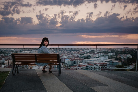 A young Caucasian woman sits on a bench and looks at the panorama of the city of Manavgat, Turkey at sunset.