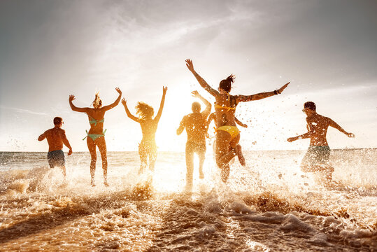 Big group of friends run and jump at sunset sea beach. Summertime holidays concept