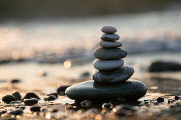 Pyramid of stones on the beach at sunset, beautiful seascape, rest and seaside vacation concept.