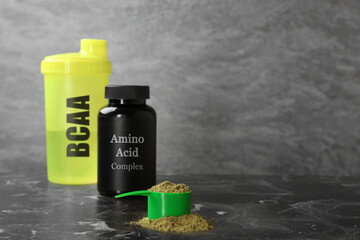 Fototapeta Shaker with abbreviation BCAA, Amino Acid complex in plastic jar and powder on table. Space for text obraz
