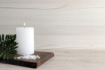 Fototapeta Burning candle, sea salt and green leaves on light beige wooden table, space for text obraz