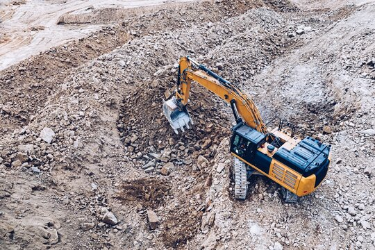 Yellow industrial excavator working on construction site. Drone view.