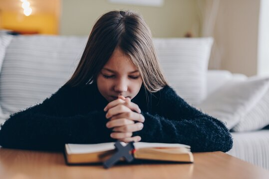 A young girl praying at home. Hope and peace concept.