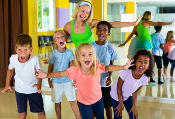 Cheerful children having fun in choreography class, posing with female trainer.