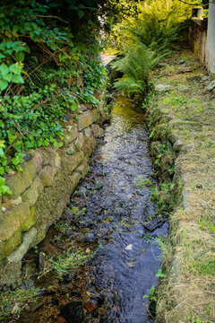 canalized small brook as flood protection measure in a village in southern germany