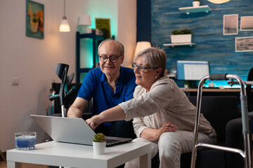 Gray haired woman old man analyzing laptop screen computer monitor at home on sofa. Retired caucasian couple using modern technology device having walk frame crutches and wheelchair