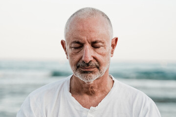 Senior man doing yoga meditation outdoor at the beach - Elderly and healthy lifestyle - Focus on face