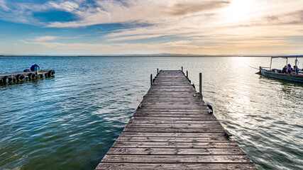 Sunset on the wooden pier or jetty on the sea with boat and couple