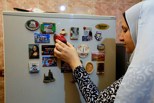 Elham Abd el-Karim, 37, a visually impaired woman touches the fridge magnets at Eman al-Hosseiny's kitchen, the author of the braille cooking book, in Cairo