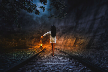 A little girl walks alone with a lantern along the railroad tracks in the middle.