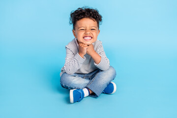 Portrait of attractive cheerful funny boy sitting on floor lotus pose grimacing isolated over bright blue color background