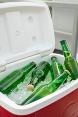Fototapeta Several green bottles of fresh cold beer in box with ice cubes obraz