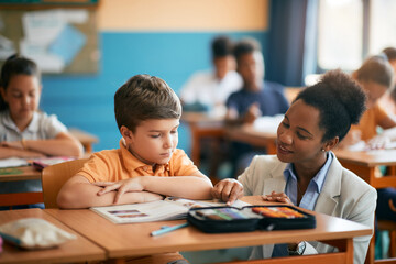 Obraz Happy African American teacher assisting her elementary student in classroom. - fototapety do salonu