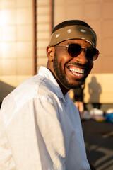 Fototapeta Cheerful African guy in white shirt, sunglasses and headband enjoying outdoor party obraz