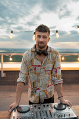 Fototapeta Young bearded deejay standing by soundboard in front of camera at rooftop patio obraz