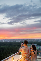 Fototapeta Young couple standing on rooftop patio while photographing colorful cloudy sky at sunset obraz