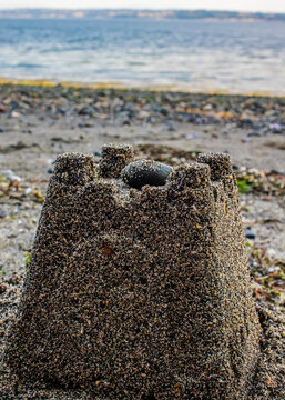 A small sandcastle on the beach of the puget sound