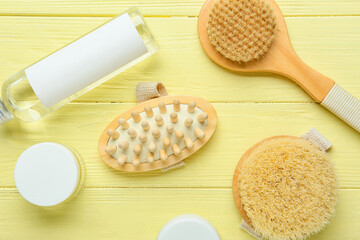 Massage brushes and different bath supplies on color wooden background