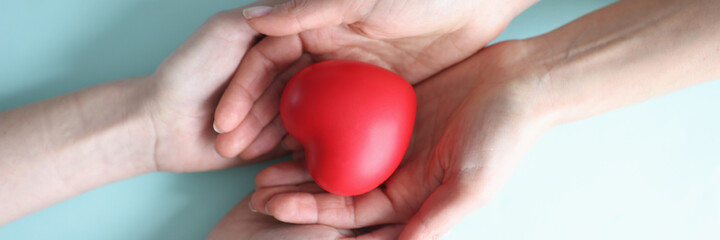 Small red heart lies in hands of two people