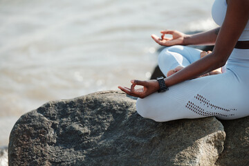 Close-up image of fit woman sitting in lotus position enjoying her calm meditation in beach