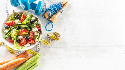 Healthy fresh salad with tomatoes surrounded with exercise equipment, carrtot celery and measuring...