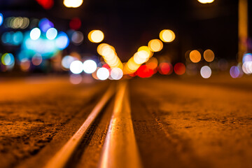 Night highway with rails, cars go over it. View from the level of asphalt