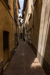 Zeer smal steegje in Bellano, Comomeer, Lombardije, Italië. Smalle steeg tussen de woongebouwen in het kleine stadje Bellano aan het Comomeer, Lombardije, Italië. Er komt maar een beetje zon onder