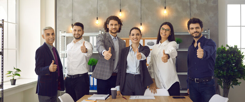 Business team is showing thumbs up by recommending the best corporate service or good career growth. Portrait of a group of different successful businessmen in the office. Concept of successful work.