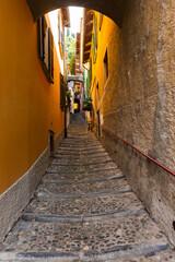 Zeer smal steegje in Varenna, Comomeer, Lombardije, Italië. Smalle steeg tussen de woongebouwen in Varenna aan het Comomeer, Lombardije, Italië. Gewoon een beetje zon komt onder in de steeg