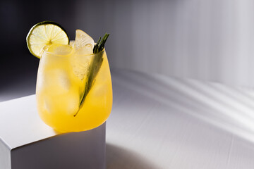 Cold orange fruit drink with ice, green rosemary, lime slice in glass on podium in elegant minimal...