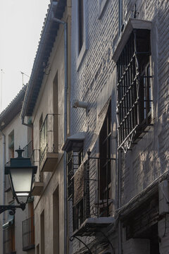 The picturesque facades of houses in historic centre of Granada lit with the sunset sun, Spain