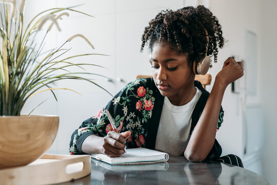 Black teenager listening to music and taking notes in notebook