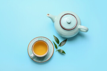 Teapot and cup of tea with green leaves on color background