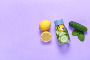 Bottle with cucumber lemonade on color background