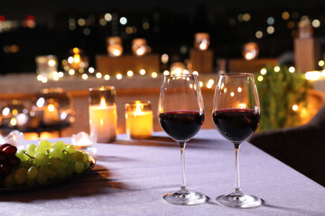 Glasses of red wine on table against blurred cityscape. Modern outdoor terrace