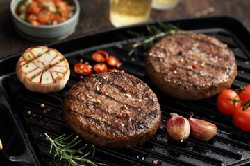 Fototapeta grelha com hambúrguer temperado, alho, pimenta, tomate e alecrim grelhados obraz