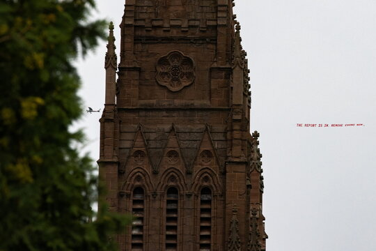 """Plane with a banner that reads """"THE REPORT IS IN, REMOVE CUOMO NOW"""" flies near a church after Attorney General's investigation found that Governor Andrew Cuomo sexually harassed multiple women, in Albany, New York"""