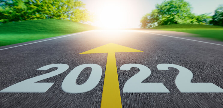 Road into evening sunset with the numbers 2022 ahead on asphalt
