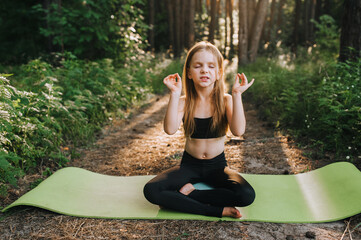 A beautiful blonde preschool girl, a child athlete professional in a black suit sits on a green rug in a lotus position and meditates, relaxes, training yoga exercises in the forest.
