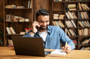 Smiling indian male employee using laptop for remote work, sits at desk in home office, talking on smartphone and taking notes, eastern man has phone conversation, writes in notepad and using laptop