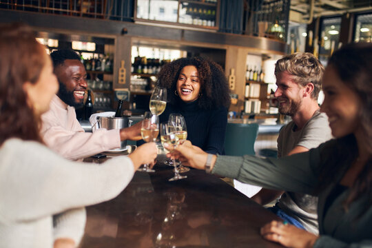 Friends celebrating with wine in bar