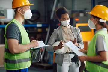 African American businesswoman discusses with warehouse workers at storage compartment.
