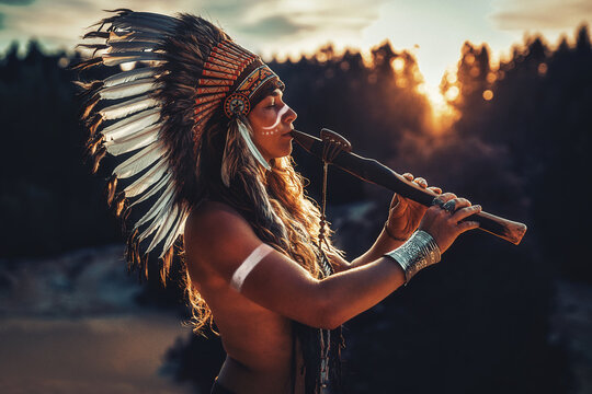 beautiful shamanic girl playing on shaman flute in the nature.