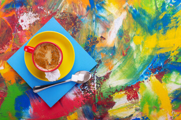 Cup of coffee and spoon with sugar at colorful abstract background texture. Coffee break