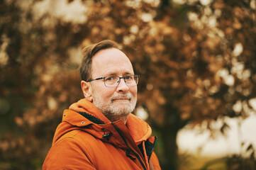 Autumn portrait of middle age man wearing orange jacket